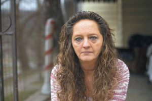 DONNA DYE, who is unemployed and whose husband is disabled, sits outside her home in Minnie, Kentucky. She and her husband have been fighting the federal government to keep his Social Security disability checks after a local lawyer who helped them became the subject of a federal fraud investigation.