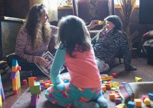 DONNA DYE, who is unemployed and whose husband is disabled, plays with her two granddaughters, Lilly, left, and Chloe at her home in Minnie, Kentucky.
