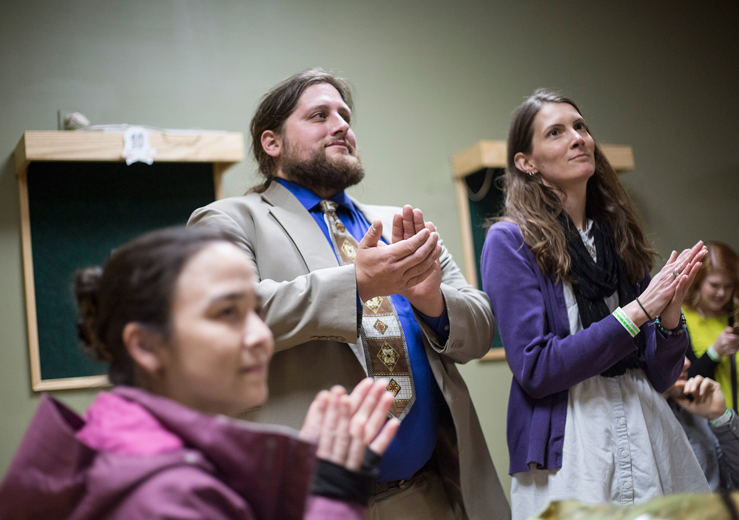 """Sherri Bukovskey of Gray, left, Paul McCarrier of Knox and his girlfriend, Carole Quigley of Monroe, applaud a speaker at Monday night's """"End of Cannabis Prohibition Party"""" at The Gold Room in Portland. Police told the event's organizers Monday afternoon that trading and consuming marijuana at the event would be a violation of the law because The Gold Room is a public space."""