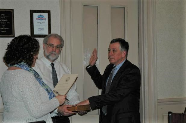 Norman Belanger, right, is sworn in Tuesday night to the Biddeford City Council at city hall by City Clerk Carmen Morris. In the center is Biddeford Mayor Alan Casavant.  LIZ GOTTHELF/Journal Tribune