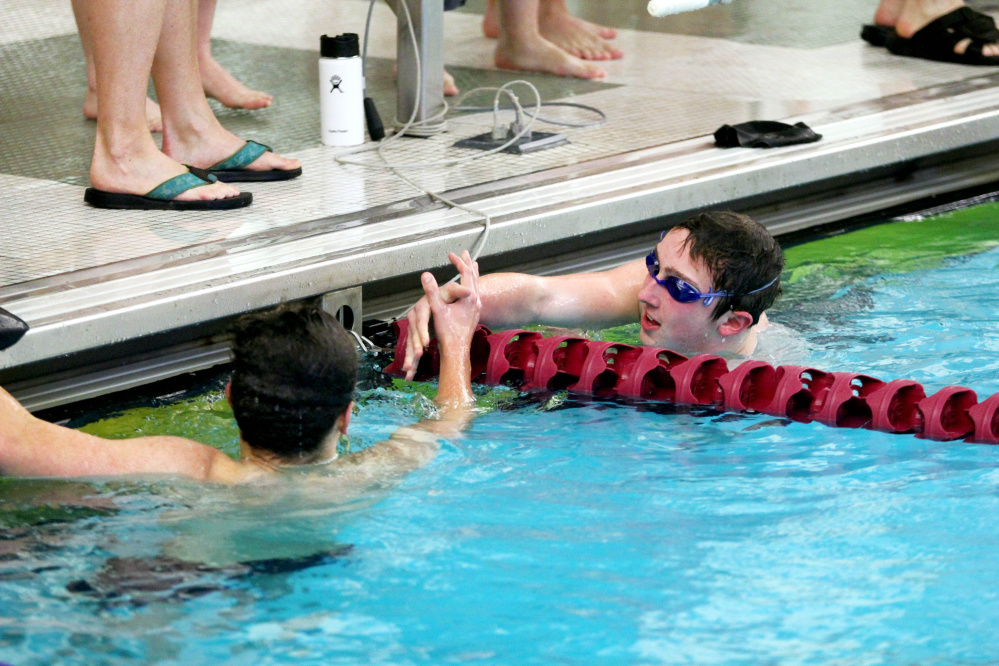 Waterville/Winslow's John Reisert is congratulated by Mt. Ararat's Deven Hoskins after winning the 500-yard freestyle at the Kennebec Valley Athletic Conference Class A meet Saturday in Bath.