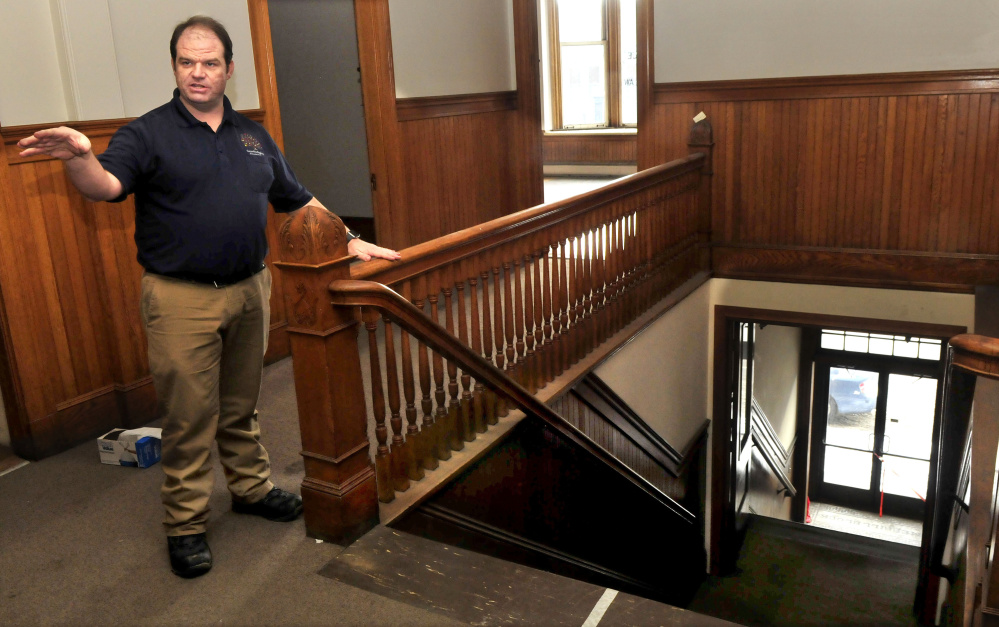 Travis Works, executive director of the Cornville Regional Charter School, points out the ornate woodwork, including the stairwell, in the former courtroom.