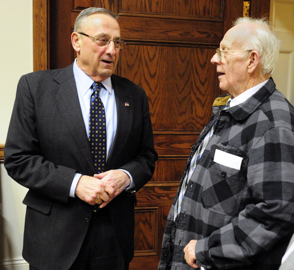 Gov. Paul LePage chats with Richard Sukeforth at a reception Tuesday night. The governor is proposing legislation to keep seniors like Sukeforth in their homes.