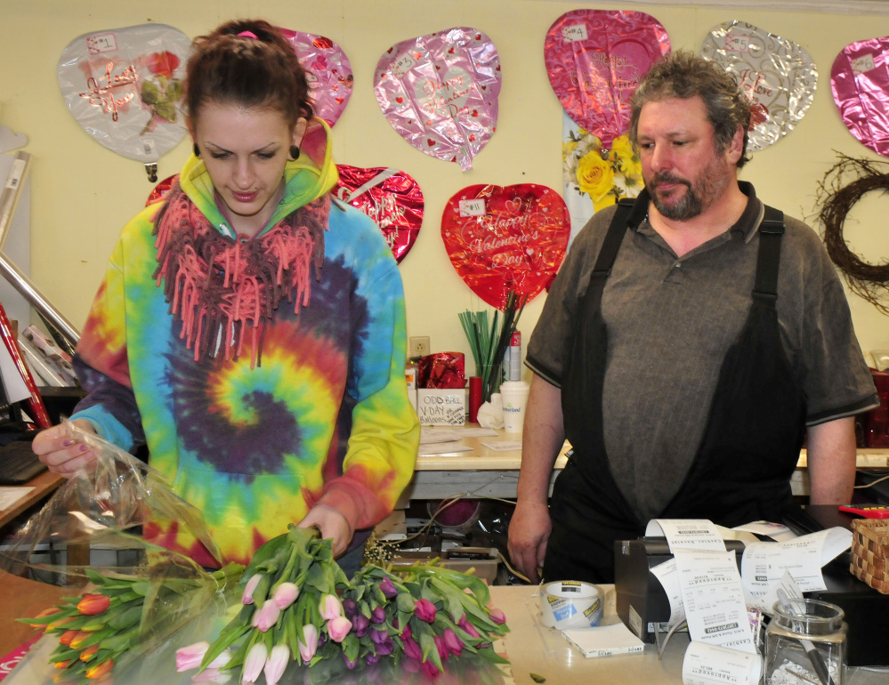 KMD Florist shop owner Dave Lagrange watches as employee Tavia Chamberlain makes a Valentine's Day bouquet at the Waterville business Monday. Maine florists are hoping for better conditions today to deliver flowers as it is one of the biggest days of the year for them.