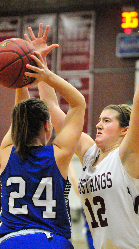 Kaylee Knowles of Searsport, left, looks to pass while guarded by Abbey Allen of Monmouth Academy during Monmouth's win in a Class C South prelim Tuesday.
