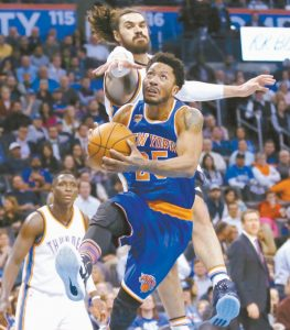 NEW YORK KNICKS guard Derrick Rose drives to the basket in front of Oklahoma City Thunder center Steven Adams, top, during the second quarter of an NBA basketball game in Oklahoma City earlier this season. The NBA regular season resumes tonight after the All-Star break.