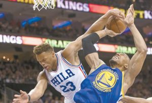 PHILADELPHIA 76ERS' Justin Anderson, left, tries to defend the shot attempt by Golden State Warriors' David West, right, but will draw the foul call during the first half of an NBA basketball game on Monday in Philadelphia.