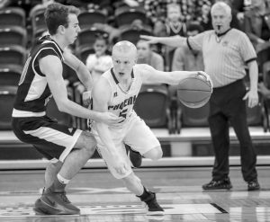 SPRUCE MOUNTAIN GUARD Austin Darling (5) looks to get by a pressing Josh Huston (20) of Lisbon late in the game during Saturday's Class B quarterfinal basketball game at the Portland Expo. The Phoenix downed the Greyhounds, 88-66.