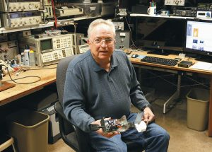 LIFELONG HAM RADIO OPERATOR and expert tinkerer Tom Thompson holds a radio wave filter he invented inside his basement home office where he operates a ham radio and other devices in Boulder, Colorado. After discovering that radio interference was being caused by high-powered lights from home marijuana growers, Thompson built an electronic filter and has given them to nearby growers.