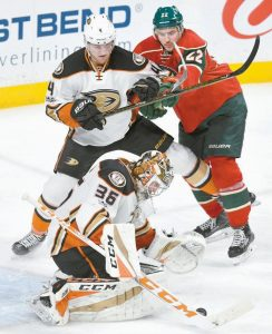 ANAHEIM DUCKS' goalie John Gibson (35) stops a Minnesota Wild shot while the Ducks' Cam Fowler, left, holds off Minnesota's Nino Niederreiter, right, in the third period of an NHL hockey game on Tuesday in St. Paul, Minn. The Ducks won, 1-0.