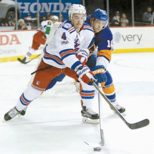 NEW YORK RANGERS' Adam Clendening (4) and New York Islanders' Ryan Strome (18) reach for the puck during the second period of an NHL hockey game on Thursday in New York.