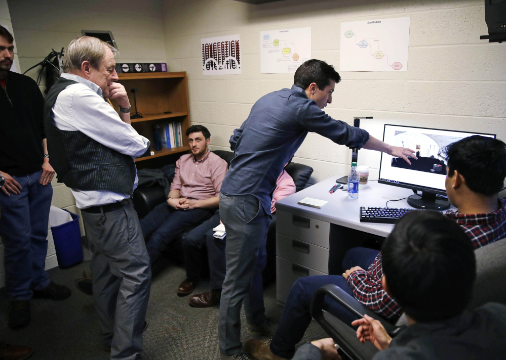 "Joseph Nugent, an English professor at Boston College, left, watches as student Evan Otero points out a graphic on a work station at the school's virtual reality lab. Students are developing a virtual reality game based on James Joyce's ""Ulysses."""
