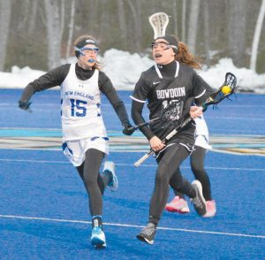 BOWDOIN COLLEGE women's lacrosse player Allison Williams, right, escapes Amber Jenkins (15) of the University of New England at the Big Blue Turf in Biddeford on Tuesday. Williams and the Polar Bears built an early lead and rolled to a 20-7 win.