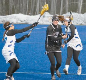 BOWDOIN'S HALSEY MCKINNEY runs down the sideline past UNE's Anna Stowell (back) and avoids the stick of Brooke Kelleher (left) during the first half of Tuesday's game.