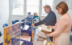 GUESTS BROWSE BOOK SELECTIONS at Curtis Memorial Library's pop-up library at the Harpswell Town Office on Tuesday. Pop-up library sessions — where folks can pick up and return books, get a library card and ask for technician's assistance — occur every Tuesday from 2-4 p.m. Below, books available at the pop-up library.