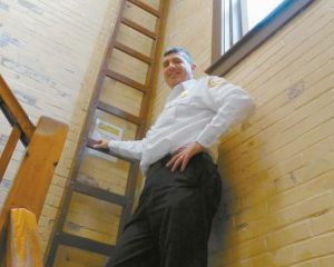 BRUNSWICK FIRE CHIEF KEN BRILLANT stands next to a ladder that had been used to access a hose tower within the staircase of Brunswick's nearly 100-year-old central fire station. The town has formed a committee to explore the needs for a new station.
