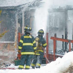 FIREFIGHTERS work to extinguish the remains of any fire the destroyed a home on Middle Road in Dresden Friday.