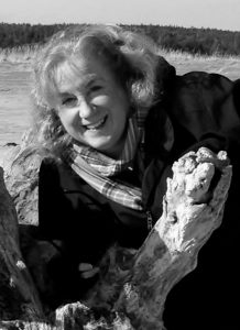JUDY PLOUFFE poses next to some driftwood on the beach near her residence in Freeport.