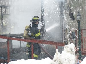 A firefighters extinguishes remaining hot spots in a home destroyed by fire on Middle Road in Dresden late Friday morning. DARCIE MOORE/THE TIMES RECORD