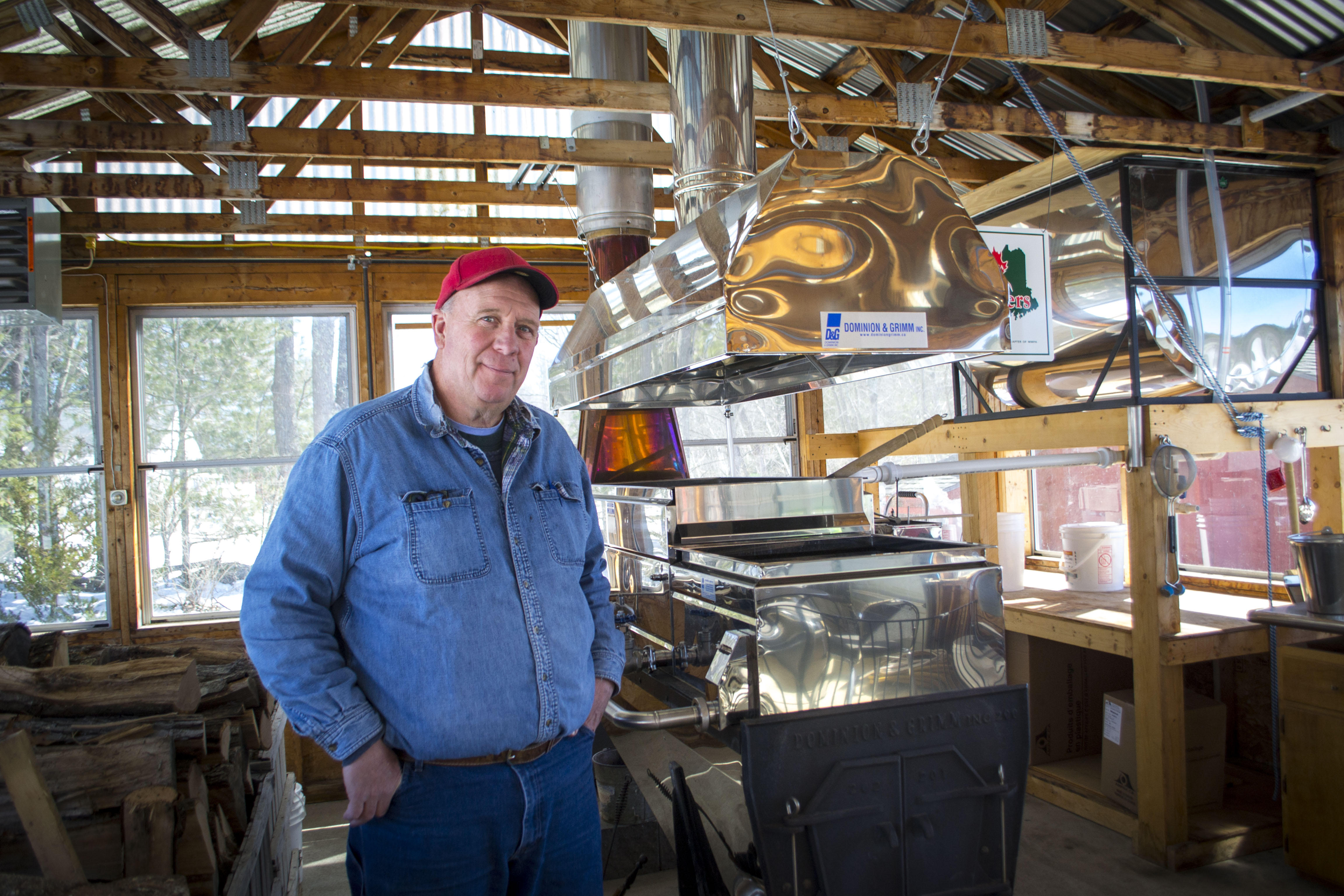 Rick Chase, of Chase Farms in Wells, stands next to his family's wood-fired maple sap evaporator on Thursday. ALAN BENNETT/Journal Tribune