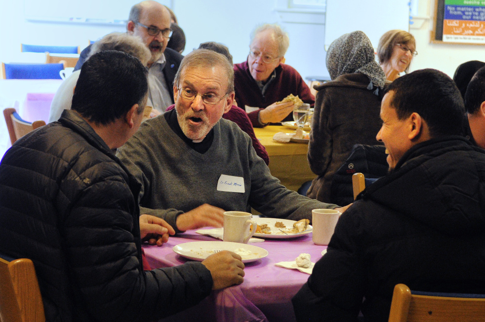 Adnan Kadhim, left, the Rev. Frank Morin, and Hassan Nasar chat over lunch on Saturday at Prince of Peace Lutheran Church in Augusta during a meeting to discuss creating a community center to welcome new residents.