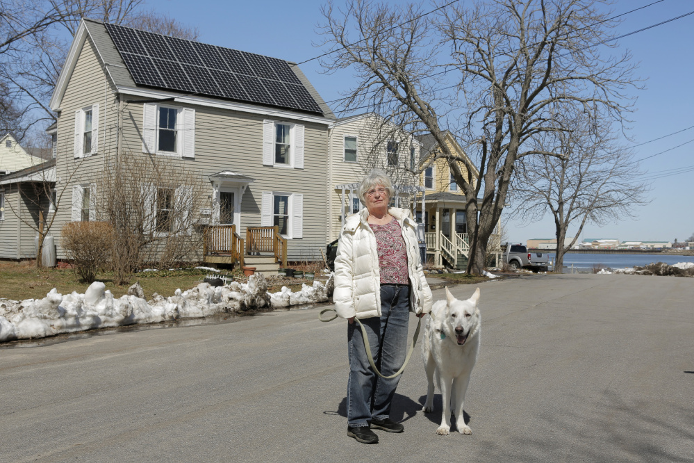 City Councilor Susan Henderson stands with her dog Jake outside her home on E Street in South Portland.