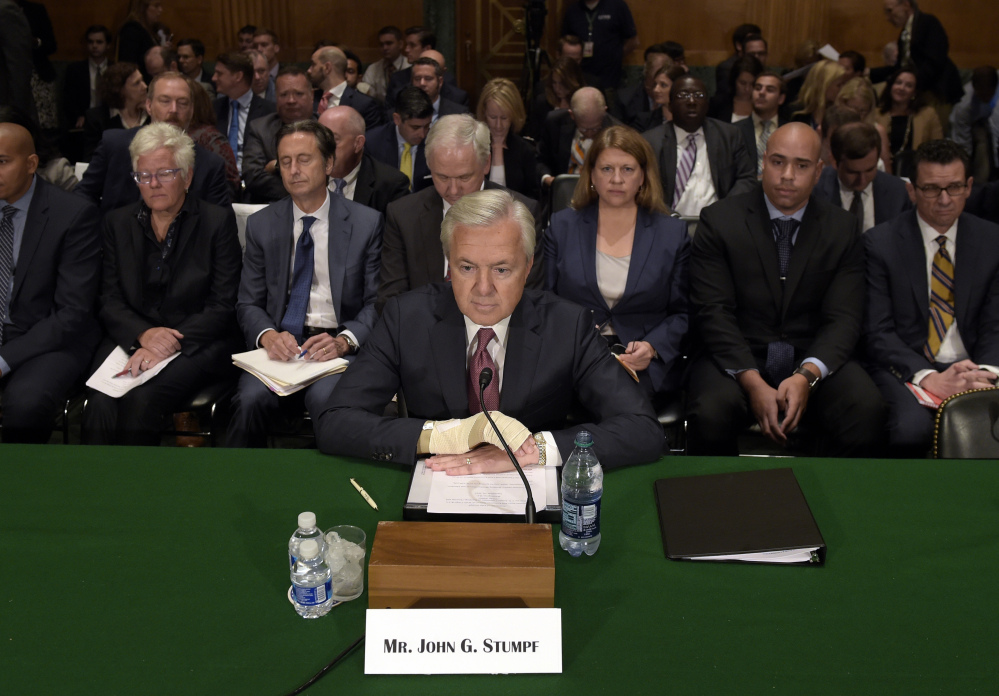 """Wells Fargo's then-CEO John Stumpf testifies before the Senate Banking Committee last September about fake accounts created by bank employees to meet sales goals. Stumpf was an optimist """"who refused to believe that the sales model was seriously impaired,"""" a directors' report says."""