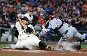 LOS ANGELES DODGERS catcher Yasmani Grandal, right, tags out San Francisco Giants' Brandon Belt at home plate after a single from Buster Posey during the first inning of a baseball game on Monday in San Francisco. The Giants won, 2-1