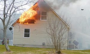 FLAMES BURST through a side of a house at 28 Hurley Drive in Richmond Wednesday afternoon.