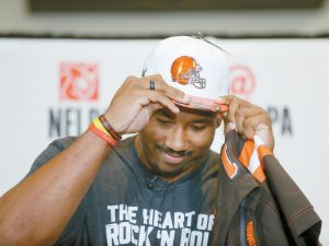 TEXAS A&M'S MYLES GARRETT puts on a Cleveland Browns hat after Garrett was taken as the No. 1 pick in the NFL football draft, at Terre Verde Golf Course in Arlington, Texas on Thursday.