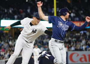 NEW YORK YANKEES relief pitcher Dellin Betances tags out Tampa Bay's Brad Miller during the eighth inning of a baseball game on Thursday in New York. The Yankees won, 3-2.
