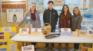 WOOLWICH CENTRAL SCHOOL social studies teacher Leanne Fisher and eighth-graders Wade Bradford, Olivia Fuller and Courtney Nicolino stand with auction items that are on display in the school's main hallway. The items will be part of the student auction that takes place on Saturday in the school gym.