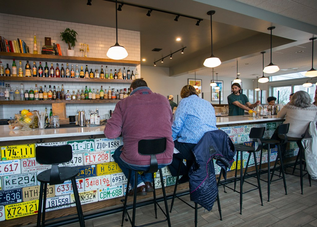 Patrons sit at the bar at Tipo, which is tiled with license plates from around the country.