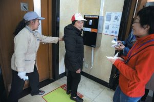 VISITORS TO THE TOILET at the Temple of Heaven park try out a facial recognition toilet paper dispenser in Beijing, China.