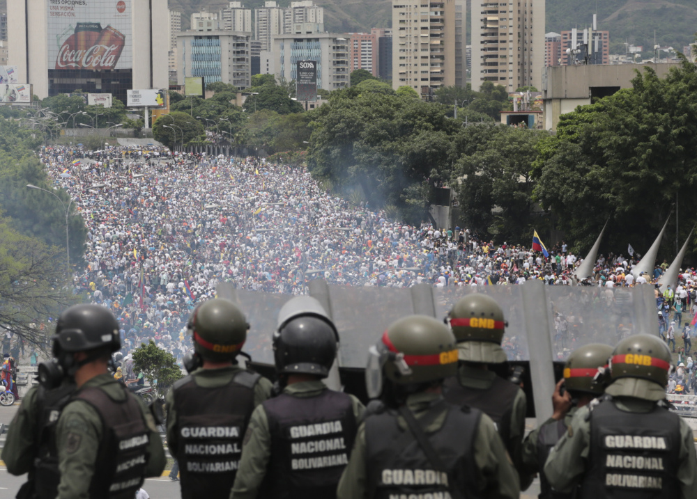 Bolivarian National Guards stand on a highway overlooking an anti-government march trying to make its way to the National Assembly in Caracas, Venezuela, Wednesday.
