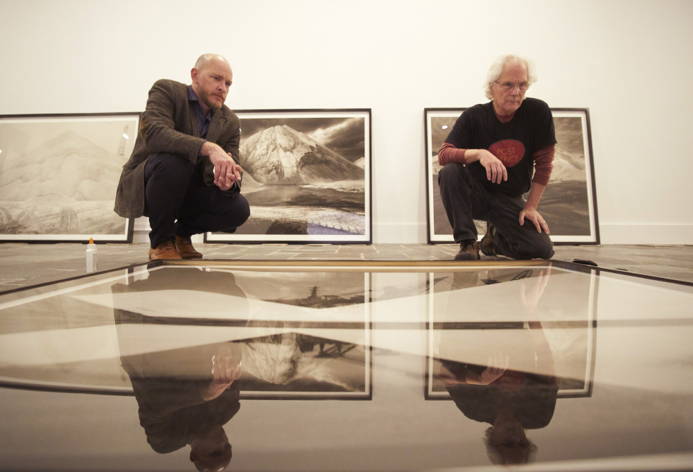 """Michael Mansfield, left, the new executive director and chief curator at the Ogunquit Museum of American Art, examines a photograph with Carl Austin Hyatt in preparation for """"Salt/Sea/Stone,"""" an exhibition of Hyatt's large-scale images."""