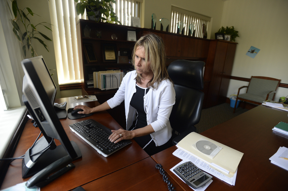 Tamika Donahue, branch manager with Residential Mortgage Services, works on new applications last Wednesday.