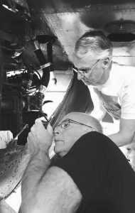 JACK MCMAHON, top, and Pat Findlay, front, work under the wing of the Vietnam-era C-123 to replace a leaking valve behind the engine in Beaver Falls. Findlay and McMahon volunteer at least a day or two every week in a large hangar at Beaver County Airport fixing up vintage aircraft at the Air Heritage Museum.