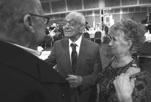 TONY AND SOPHIA GEORGE talk with one of many friends during their 70th wedding anniversary party in Macomb, Michigan.