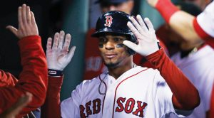 BOSTON'S XANDER BOGAERTS is congratulated by teammates after scoring on a double by Chris Young during the fourth inning of a baseball game against the Baltimore Orioles at Fenway Park in Boston on Wednesday. The Red Sox won, 4-2.