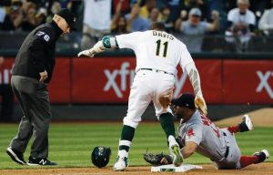 OAKLAND'S Rajai Davis (11) is tagged trying to stretch a double into a triple after stepping off the bag at third by Boston Red Sox third baseman Deven Marrero during the third inning of a baseball game on Thursday in Oakland, Calif.