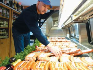 ANDRE BONNEAU straightens sausage on display in his family's store, Maurice Bonneau's Sausage Kitchen in Lisbon Falls. It was founded by his father.