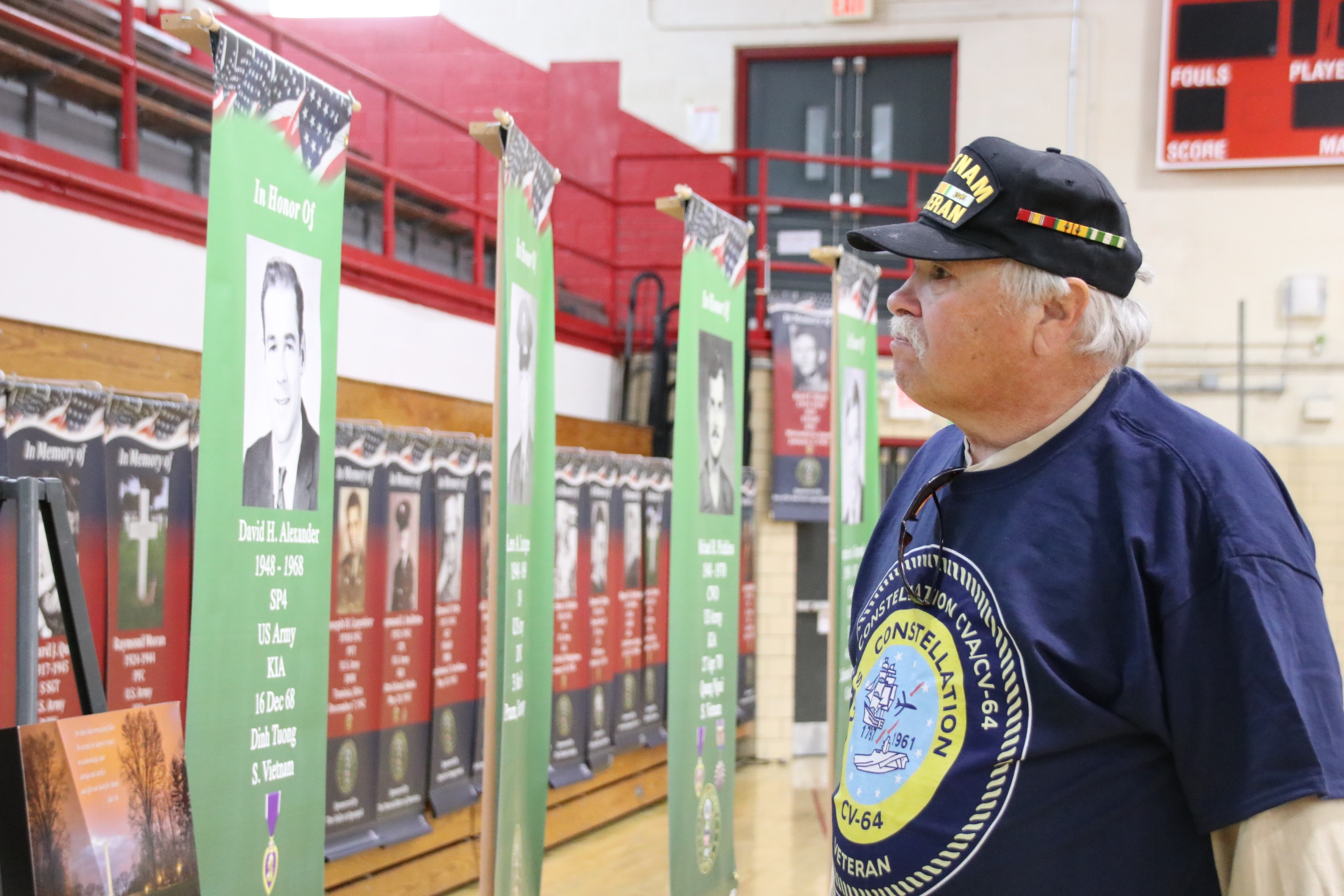John Crystal of Sanford, a U.S. Navy veteran of the Vietnam War, looks at banners depicting fellow service members who were killed in action during a memorial ceremony at Sanford Veterans Memorial Gym in Sanford Tuesday. TAMMY WELLS/Journal Tribune