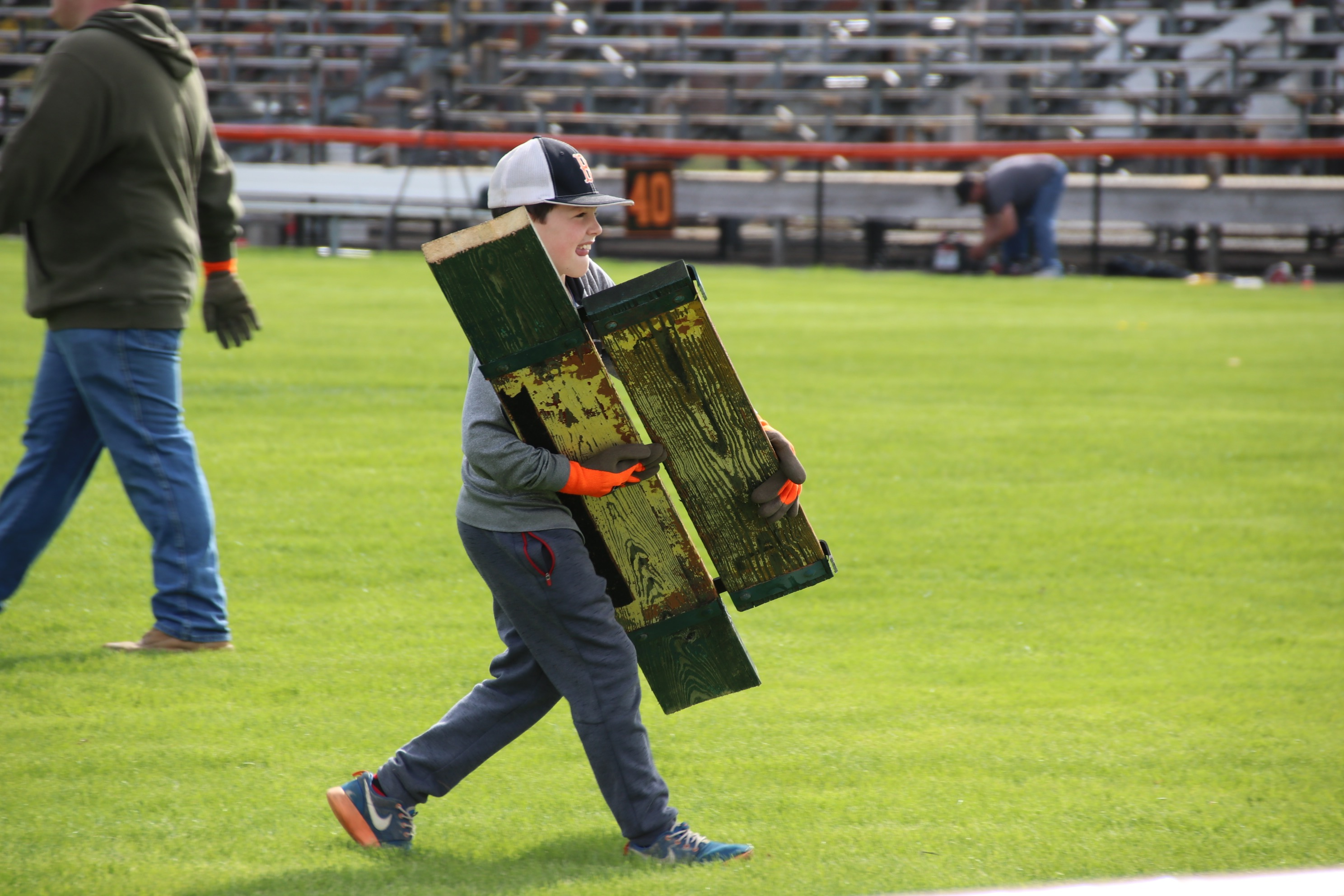 Travis Edgerton, 9, carries parts of an old bleacher seat across Waterhouse Field Saturday, where the wood was being stacked and is  eventually destined to be reclaimed. He and about 199 others — young, old and in between — gathered at the field to get the old, unsafe bleachers down. TAMMY WELLS/Journal Tribune