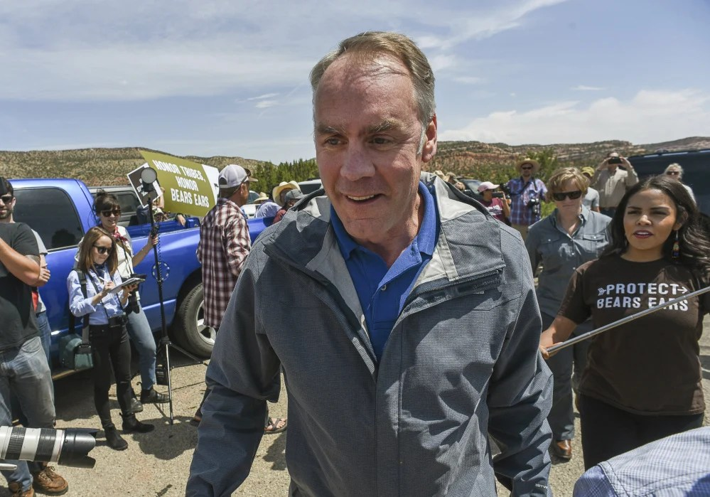 FILE - In this May 8, 2017, file photo, U.S. Interior Secretary Ryan Zinke arrives at the Butler Wash Indian Ruins trail head within Bears Ears National Monument in Utah as supporters of the monument crowd the parking lot. Zinke will have tens of thousands of comments to potentially look over as he prepares a recommendation next month for President Donald Trump about whether the new Bears Ears National Monument should be preserved, downsized or rescinded. (Francisco Kjolseth /The Salt Lake Tribune via AP)