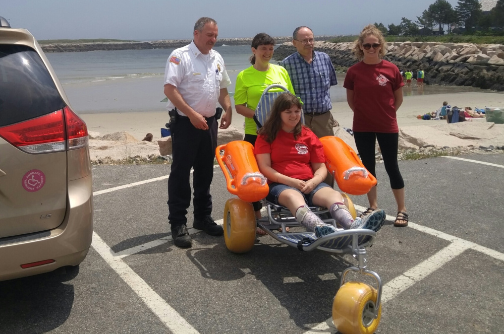 Smile Mass co-founder Susan Brown, second from left, presents a donated floating wheelchair to, from left, Wells Fire Chief Wayne Vetre, Town Manager Jonathan Carter and lifeguard captain Emily Bordeau. Kristen Brown is seated in the wheelchair . Photo courtesy of Linda Rizzo