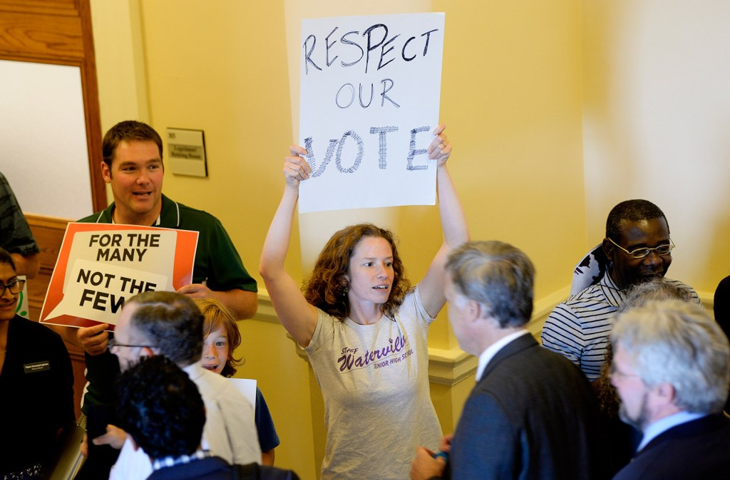 Ciara Hargrove, a teacher in Waterville, protests at the State House on Tuesday against a state shutdown.