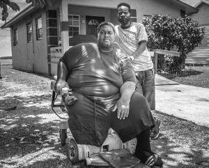 DARRYL HENDERSON, left, a former homeless resident of South Bay, sits in his motorized wheelchair next to his childhood friend who he is temporarily living with, Taurance Lovely.