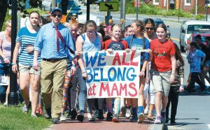"""MT. ARARAT MIDDLE SCHOOL students carry the """"We All Belong"""" message as they walk down Main Street on Wednesday toward the Green Bridge between Topsham and Brunswick to meet with Brunswick Junior High School students."""