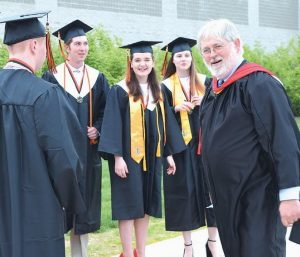 CLARK PORTER, a math teacher at Brunswick High School, is greeted by students outside of Watson Arena on Friday just prior to the start of the graduation ceremony.
